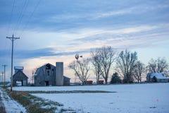 Dunkel himmel för molnig vinter över den gamla övergivna lantgård och väderkvarnen royaltyfri bild