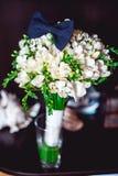 Dunkelblaue Fliege auf einem Luxusbrautblumenstrauß von weißen Blumen auf einem Regal Stockfotografie