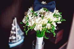 Dunkelblaue Fliege auf einem Luxusbrautblumenstrauß von weißen Blumen auf einem Regal Stockbild