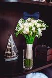 Dunkelblaue Fliege auf einem Luxusbrautblumenstrauß von weißen Blumen auf einem Regal Stockfotos