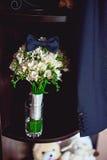 Dunkelblaue Fliege auf einem Luxusbrautblumenstrauß von weißen Blumen auf einem Regal Stockbilder