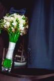 Dunkelblaue Fliege auf einem Luxusbrautblumenstrauß von weißen Blumen auf einem Regal Lizenzfreies Stockbild