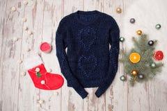Dunkelblaue gestrickte Strickjacke auf einem hölzernen Hintergrund Tannenbaumniederlassung mit den Weihnachtsdekorationen, auf La Stockbild