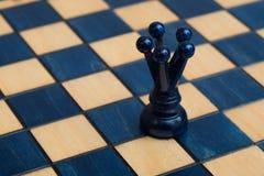 Dunkelblaue Königin auf hölzernem Schachbrett Stockbild