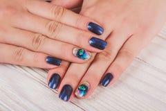 Dunkelblaue Nagelkunst mit Druckauge stockfotos
