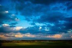 Dunkelblaue Wolken, die über grüne Felder sich bewegen Landwirtschaftliche Landschaft lizenzfreie stockfotos