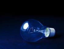 Dunkelblaue zurückhaltende Hintergrundkonzeption der Glühlampe für die Idee kreativ Stockfoto