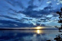Dunkelblauer Abendhimmel über dem See, orange Sonne Lizenzfreies Stockfoto
