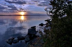 Dunkelblauer Abendhimmel über dem See, orange Sonne Stockfoto