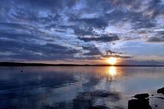 Dunkelblauer Abendhimmel über dem See, orange Sonne Stockfotos
