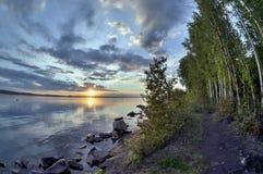 Dunkelblauer Abendhimmel über dem See, orange Sonne, Türspion Lizenzfreie Stockfotografie
