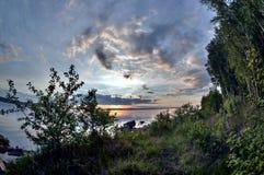 Dunkelblauer Abendhimmel über dem See, orange Sonne, Türspion Lizenzfreie Stockbilder