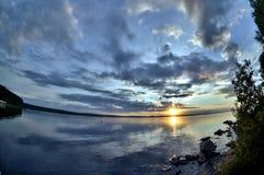 Dunkelblauer Abendhimmel über dem See, orange Sonne, Türspion Stockfotografie