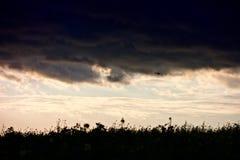 Dunkelblauer beunruhigender Himmel nach einem Sturm mit einem Hubschrauber in den Wolken lizenzfreie stockbilder