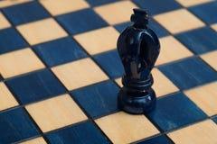 Dunkelblauer König auf hölzernem Schachbrett Stockbild