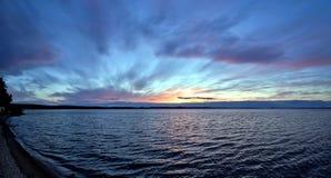 Dunkelblauer und orange Abendhimmel über dem See Stockfotos