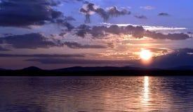 Dunkelblauer und orange Abendhimmel über dem See Lizenzfreie Stockfotos