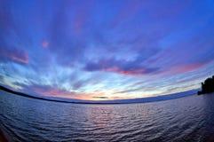 Dunkelblauer und orange Abendhimmel über dem See, Türspion Stockfotos