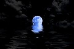 Dunkelblauer Vollmond in der Wolke mit Wasserreflexion stockfoto