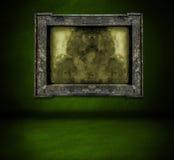 Dunkelgrüne Wand mit Rahmen- und Bodeninnenraumhintergrund Stockfoto