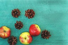 Dunkelgrüner Hintergrund mit Kiefernkegeln, rote Äpfel auf dem hölzernen Lizenzfreies Stockfoto