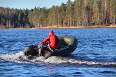 Dunkelgrünes, aufblasbares Schlauchbootboot mit Motor, Waldlak lizenzfreie stockbilder