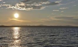 Dunkelgrauer Abendhimmel über dem See, orange Sonne Stockbilder