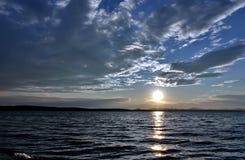 Dunkelgrauer Abendhimmel über dem See, orange Sonne Lizenzfreies Stockfoto