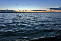Dunkelgrauer Abendhimmel über dem See, orange Sonne Stockfotografie
