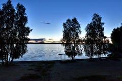 Dunkelgrauer Abendhimmel über dem See, orange Sonne Lizenzfreies Stockbild