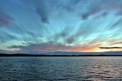 Dunkelgrauer Abendhimmel über dem See, orange Sonne Lizenzfreie Stockbilder
