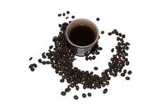 Dunkelgrauer Tasse Kaffee besprüht mit Körnern des Kaffees auf einem whi Stockbild