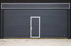 Dunkelgraues modernes Garagentor mit kleiner Tür Stockbild