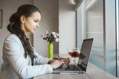 Dunkelhaarige Frau, die auf Laptop schreibt Tageslicht vom Fenster belichtet Tabelle stockfoto