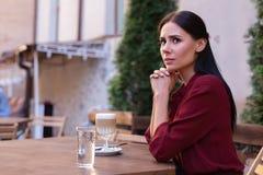 Dunkelhaarige Frau, die beim Warten auf ihren Freund gesorgt glaubt Stockbild
