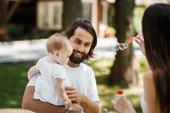 Dunkelhaarige Frau, die Seifenblasen im Freien macht Vater mit Tochter in den Armen, die aufmerksam sie und das Lächeln betrachte lizenzfreies stockfoto