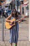 Dunkelhaarige Sängerin auf Straße mit Sonnenbrille und stockbild