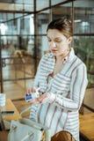 Dunkelhaarige schwangere Frau, die Vitamine und Ergänzungen nimmt lizenzfreie stockfotografie