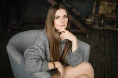 Dunkelhaarige traurige Frau im langen Grau strickte die gemütliche Strickjacke, die zu Hause in einem Stuhl nahe großem Fenster s stockfotografie