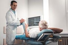 Dunkelhaariger Doktor in der weißen Uniform Knochen überprüfend stockbild