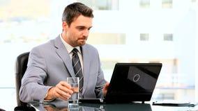 Dunkelhaariger Geschäftsmann, der an seinem Laptop arbeitet stock video footage