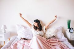 Dunkelhaariger schöner junger Brunette in ihrem Bett aufwachen Ausdehnen herauf Hände und Lächeln Schlafenmaske auf Stirn Allein lizenzfreies stockbild