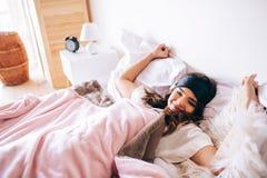 Dunkelhaariger schöner junger Brunette in ihrem Bett aufwachen Ausdehnen von Händen und bosdy L?gen auf Bett im Schlafzimmer Alle stockfotos