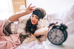Dunkelhaariger schöner junger Brunette in ihrem Bett aufwachen Gereizte Frau, die heraus liegt und erreicht, um abzustoppen Griff lizenzfreie stockfotografie
