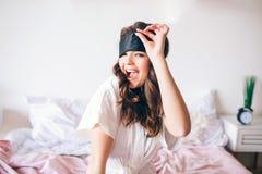 Dunkelhaariger schöner junger Brunette in ihrem Bett aufwachen Positive attraktive Frau, die auf Kamera und Lächeln aufwirft Halt stockfotografie