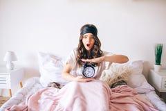 Dunkelhaariger schöner junger Brunette in ihrem Bett aufwachen Verwirrte Frauengriffuhr in den Händen Wachte später auf Überrasch stockfoto