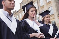 Dunkelhaariger Student, der an ihrem Graduierungstag empfindlich sich fühlt lizenzfreie stockfotografie