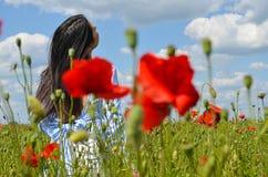 Dunkelhaariges schönes Modell, das auf dem Mohnblumengebiet von Blumen aufwirft stockfoto
