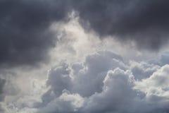 Dunkelheit gegen helles Cloudscape Stockfotografie