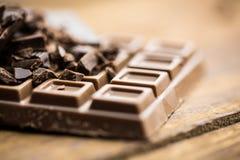 Dunkelheit und Milchschokolade auf einem Holztisch Stockfotografie